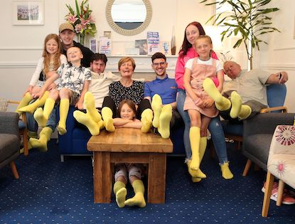 Image of people wearing yellow socks sat together