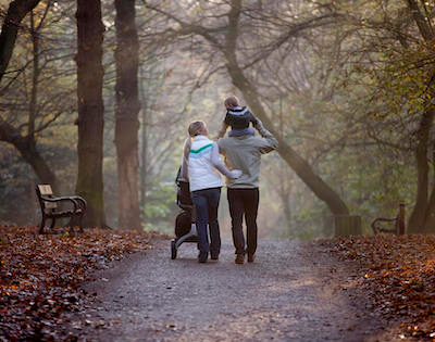 Two people walking in woodland with a small child
