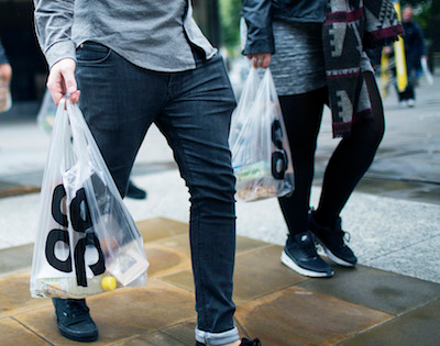 people walking with a co-op shopping bag