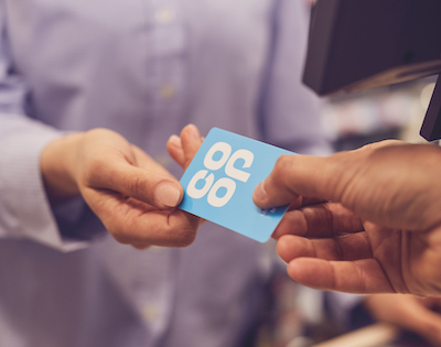 Image of a person handing over their membership card to a Co-op staff member