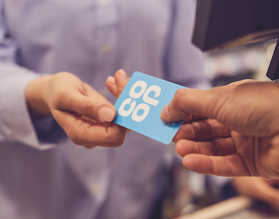 A customer handing a Co-op Membership Card across to a member of staff