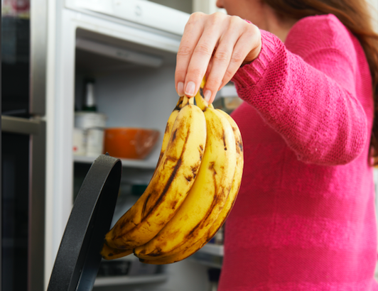 A woman dropping a bunch of old looking bananas into the bin
